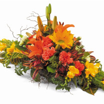Horizontal arrangement in floral foam containing a selection of seasonal flowers and foliages